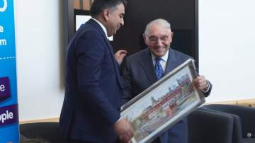 Sir Norman Stoller receives an annotated artists print of the Mumps railway bridge emblasoned with the greeting - Welcome to Oldham home of the tubular bandage'